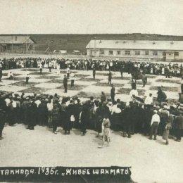 Партия в «живые шахматы» - одна из интереснейших форм пропаганды этой игры. Она проводится на доске гигантского размера, размеченной на открытой площадке. На фотографии запечатлена партия в «живые шахматы», сыгранная в Охе в 1935 году. Пешки и фигуры изображают люди. В правом нижнем углу видно, как на носилках уносят с доски срубленную «пешку». Кони, как видите, настоящие. Стоят и ждут момента, когда можно будет сделать ход буквой «г». Слонов, правда, живых нет. Уж чего-чего, а вот слонов на Сахалине днем с огнем не сыщешь, что в 1935 году, что сейчас… И обратите внимание, сколько вокруг доски болельщиков! Несколько сотен зрителей точно есть, а то и тысяча-другая…