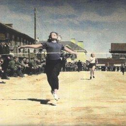 В начале 1950-х годов легкая атлетика в Охе была чрезвычайно популярна. Состязания неизменно проходили при большом количестве болельщиков. В этот раз они наблюдают за женским забегом на 100 метров. Это одна из первых цветных фотографий в истории сахалинского спорта.